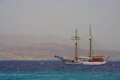 走在一条木小船在红海,以色列,有他们的风帆和山的在背景中 免版税库存图片