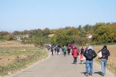 走在一条路的专栏的难民在途中到克罗地亚塞尔维亚边界,在巴尔干路线 免版税库存图片