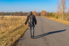走在一条路的背包徒步旅行者在乌克兰乡区在秋季 免版税库存图片