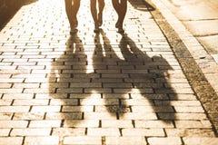 走在一条边路的三个女孩的阴影在城市 库存照片
