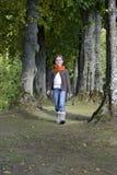 走在一条道路的女孩在森林里 免版税图库摄影