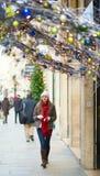 走在一条巴黎人街道上的女孩在圣诞节 免版税库存照片