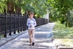 走在一条晴朗的街道上的小男孩 免版税库存图片