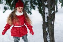 走在一棵树下的美丽的女孩在冬天 免版税库存图片