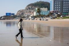 走在与一张被盖的面孔的海滩的女孩 免版税库存图片