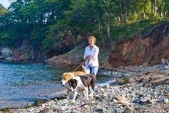 走在与两条狗的海滩附近的少妇 免版税图库摄影
