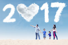 走在与云彩的海滩的家庭2017年 库存图片