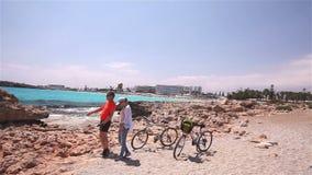 走在与他们的自行车的海滩的无忧无虑的夫妇在慢动作 股票视频