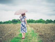 走在与伞的无油气地区的妇女 库存照片