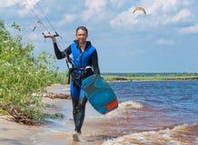 走在与冲浪板的海滩的风筝冲浪者 库存图片
