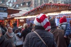 走在与圣诞节帽子的圣诞节市场上的人们 免版税库存照片