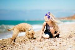 走在与小狗狗的海滩的小女孩 免版税库存照片
