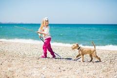 走在与小狗狗的海滩的小女孩 免版税图库摄影