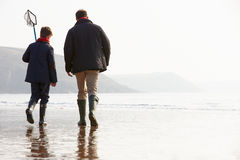 走在与捕鱼网的冬天海滩的父亲和儿子 图库摄影