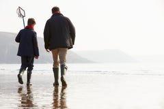 走在与捕鱼网的冬天海滩的父亲和儿子 免版税图库摄影