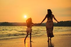 走在与日落的海滩的母亲和女儿 免版税库存照片