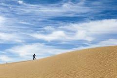 走在与有趣的云彩的沙丘的一个人在背景中 免版税库存照片