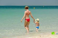 走在与母亲的海滩的小孩男孩 库存图片