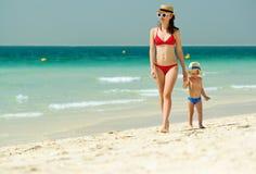 走在与母亲的海滩的小孩男孩 免版税库存照片