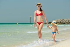 走在与母亲的海滩的小孩男孩 免版税图库摄影