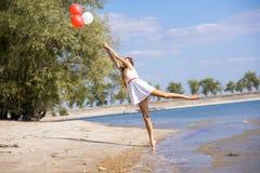 走在与气球的海滩的女孩 库存图片