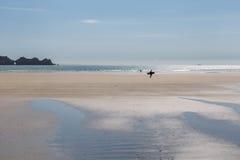走在与海和岩石c的宽含沙夏天海滩的冲浪者 库存图片