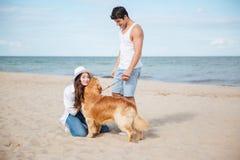 走在与狗的海岸的浪漫年轻夫妇 免版税库存图片