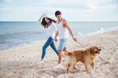 走在与狗的海岸的浪漫年轻夫妇 库存图片