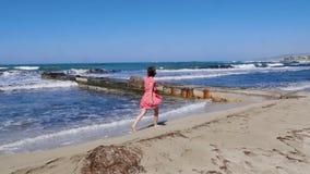走在与穿红色礼服的海码头的沙滩的年轻可爱的妇女 飞溅反对码头和海的强的波浪 股票录像