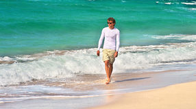 走在与蓝色海的海滩海边沙子的英俊的人背景的 免版税库存照片