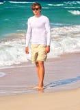 走在与蓝色海的海滩海边沙子的英俊的人背景的 库存照片
