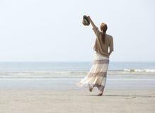走在与被举的胳膊的海滩的妇女 免版税库存图片