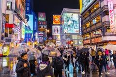 走在五颜六色的夜的拥挤人民下雨在Dotonbori大街的街道 免版税库存照片