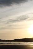 走在五颜六色的日出夏天天空的沙滩的人风景剪影与反射 免版税图库摄影