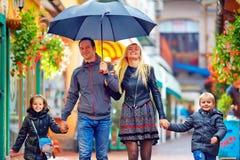 走在五颜六色的街道上的雨下的愉快的家庭 库存照片
