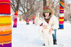 走在五颜六色的装饰的树之间的男孩和他的小姐妹在一个多雪的公园 免版税库存照片