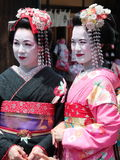 走在京都老镇艺妓区日本的美丽的年轻和成熟艺妓 免版税库存照片