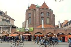 走在人群和循环通过著名Viktualienmarkt商店的人们  免版税库存照片