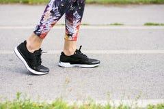 走在体育鞋子的公园的少妇 免版税库存图片