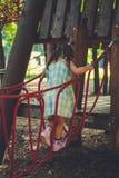 走在儿童` s操场的一座猴子桥梁的小女孩 免版税图库摄影
