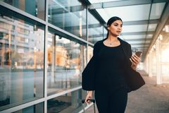 走在公共交通驻地之外的女实业家 免版税图库摄影