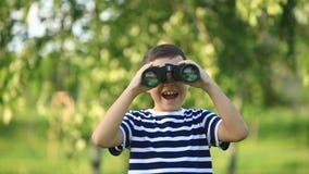 走在公园和看通过双筒望远镜的小男孩