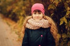 走在公园或森林的美丽的愉快的儿童女孩秋天室外画象  免版税库存图片
