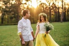 走在公园的一对爱恋的夫妇在日落 库存照片