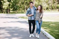 走在公园的一对年轻夫妇的画象 库存照片