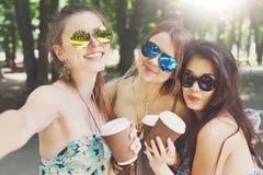 走在公园的三个美丽的年轻boho别致的时髦的女孩 免版税库存照片