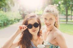 走在公园的两个美丽的年轻boho别致的时髦的女孩 库存图片