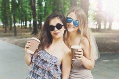 走在公园的两个美丽的年轻boho别致的时髦的女孩 免版税库存照片