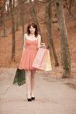 走在公园的典雅的顾客妇女在购物以后 免版税库存图片