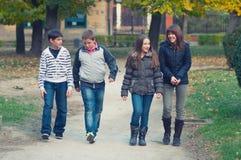走在公园的十几岁的男孩和女孩在五颜六色的春日 免版税图库摄影